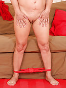 57 yr old Lena F as part of sensuous red lingerie spreads the lady legs regarding the sofa