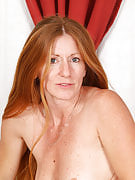 Redheaded MILF as part of purple lingerie wows you with her body